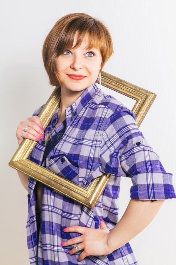 Young thin Woman peers out from the photo frame wearing blue checkered cotton shirt, over white background stock images