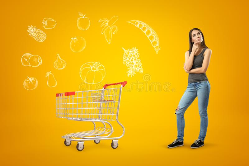 Young thinking brunette girl wearing casual jeans and t-shirt with shopping cart and cartoon food drawn on yellow stock photography