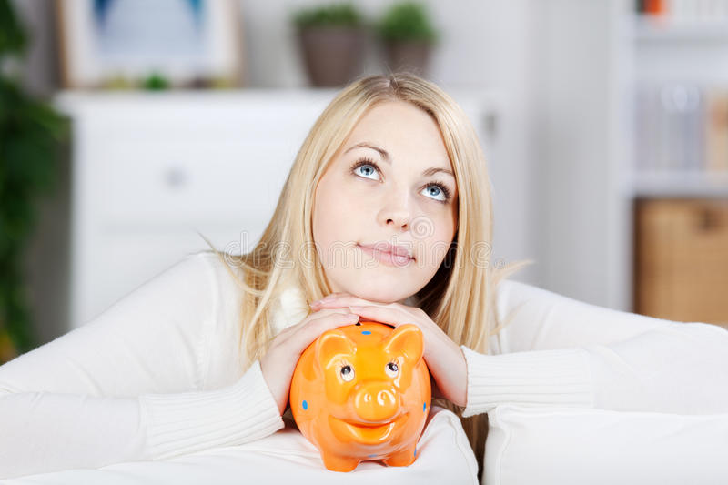 Young Thinking Woman Holding Orange Piggy Bank royalty free stock images