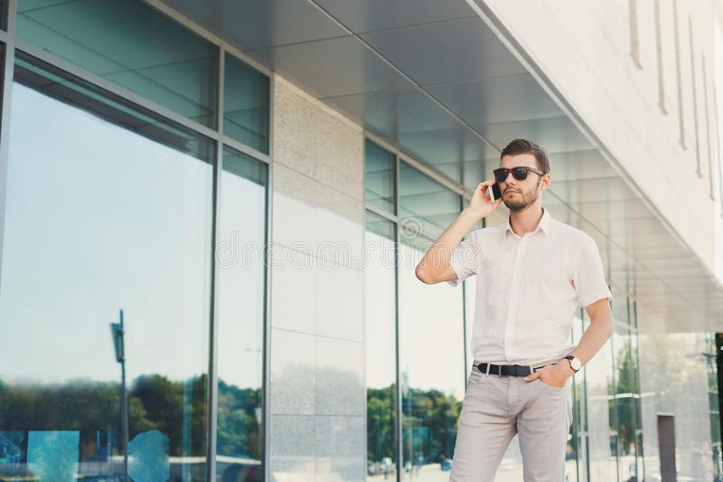 Young thoughtful businessman making a phone call outdoors royalty free stock photo