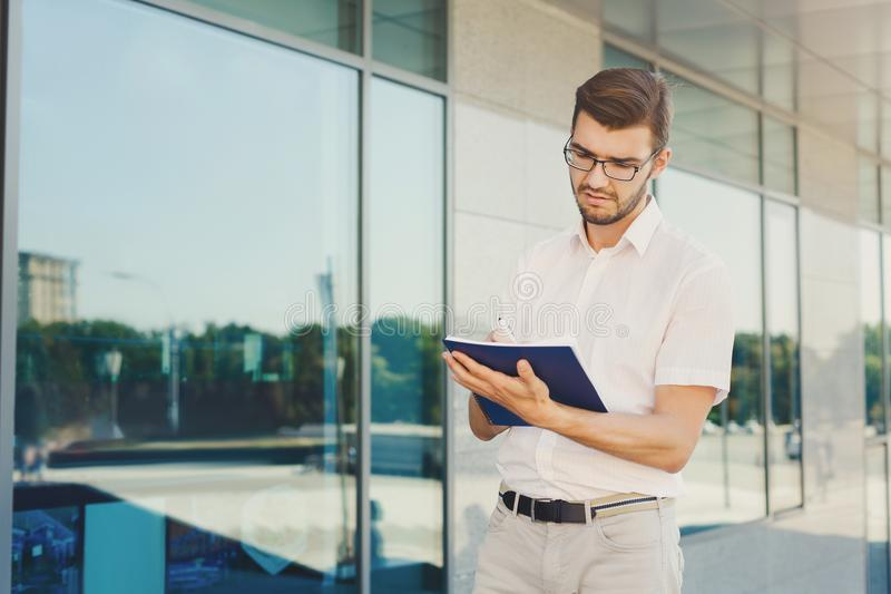 Young thoughtful businessman writing in notepad stock images