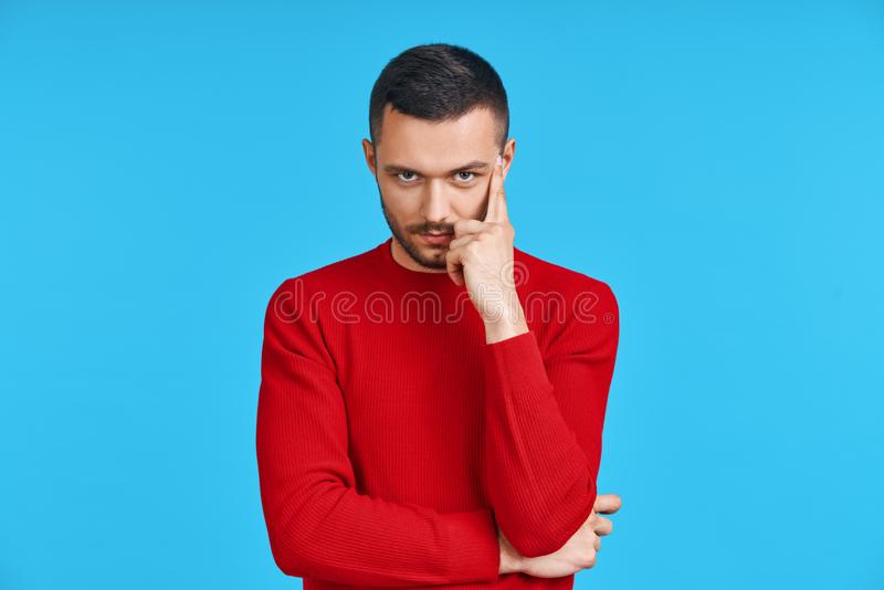 Young thoughtful man thinking and looking to camera with copy space, isolated on blue background stock photography