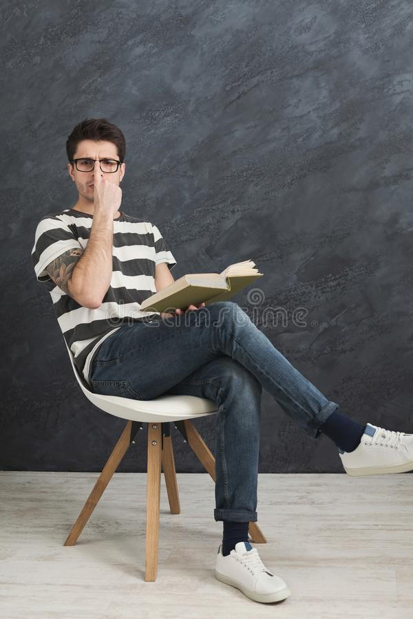 Young thoughtful tattooed man with book stock image