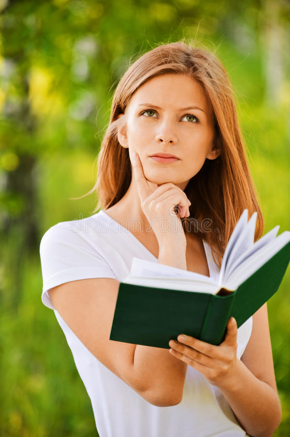Young thoughtful woman holding book. Portrait of young attractive pensive woman looking to sky and holding green book, standing at summer park stock photos