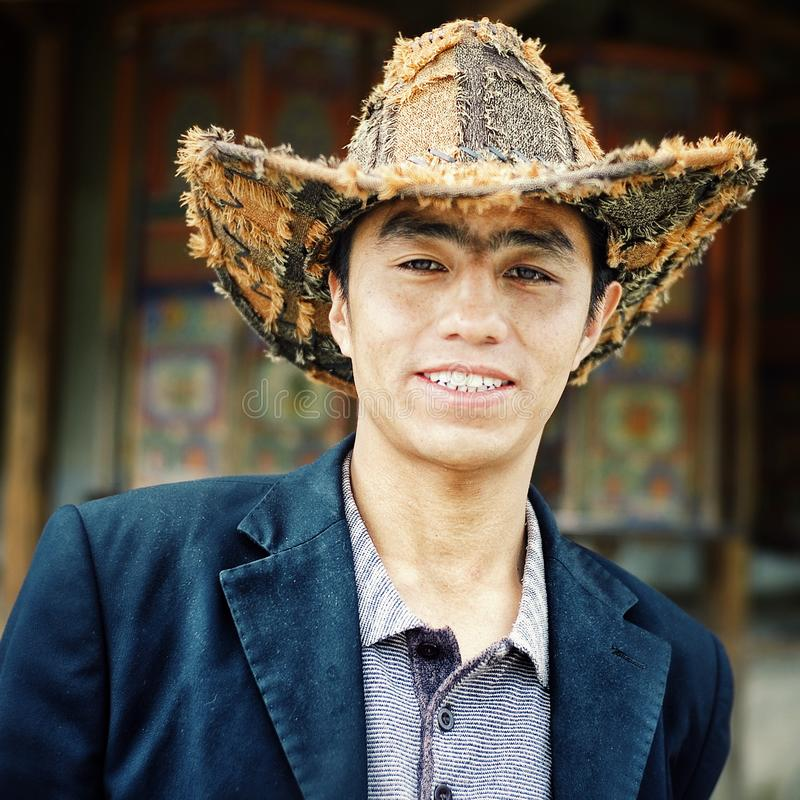 young tibetan buddhist pilgrim man with a strange hat waiting in front of the prayer wheels royalty free stock image