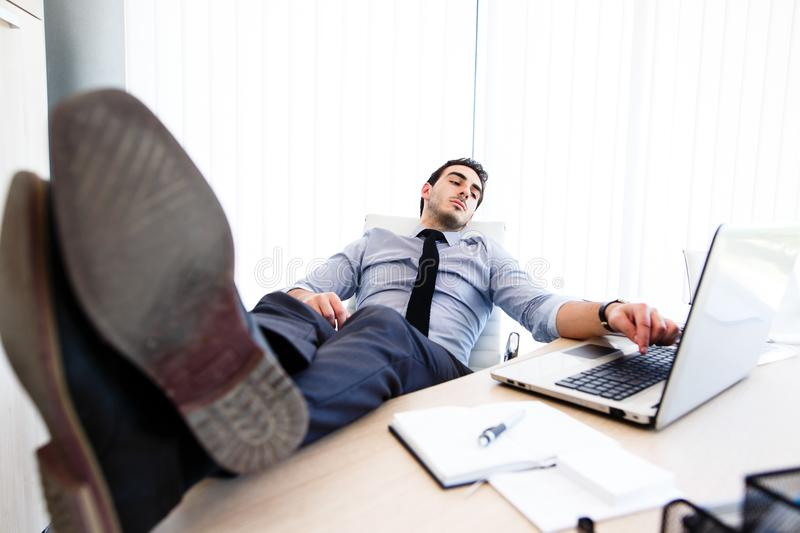 Young tired business man at workplace.  royalty free stock photo