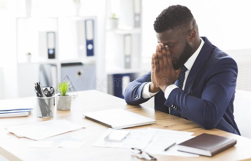 Young tired businessman having stress at work. Young tired african american businessman having stress at work, sitting with closed eyes at workplace, empty space stock image