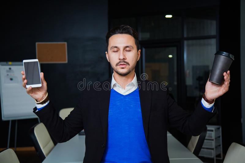 Young tired businessman meditating on table with mobile phone and coffee royalty free stock photography
