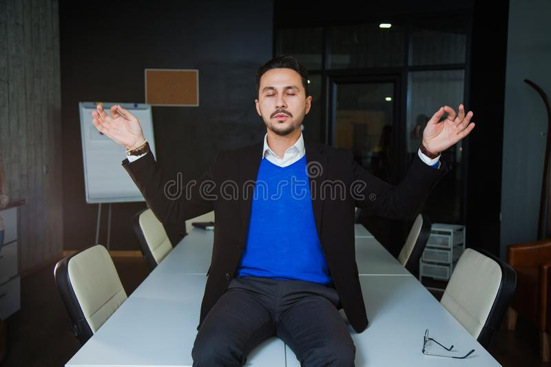 Young tired businessman meditating on office table royalty free stock image