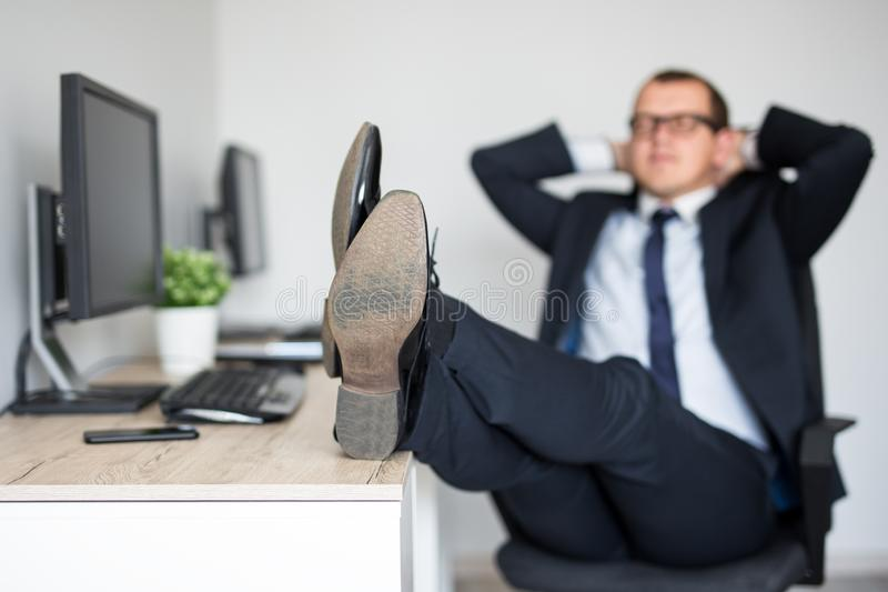 Tired businessman relaxing in modern office sitting with legs on the table stock image