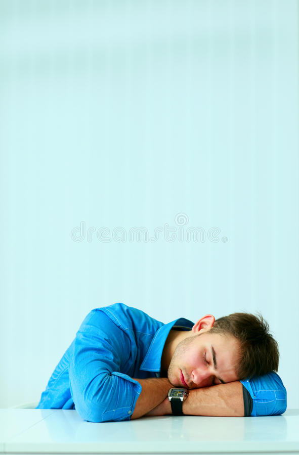 Young tired businessman sleeping at workplace. In office royalty free stock photography