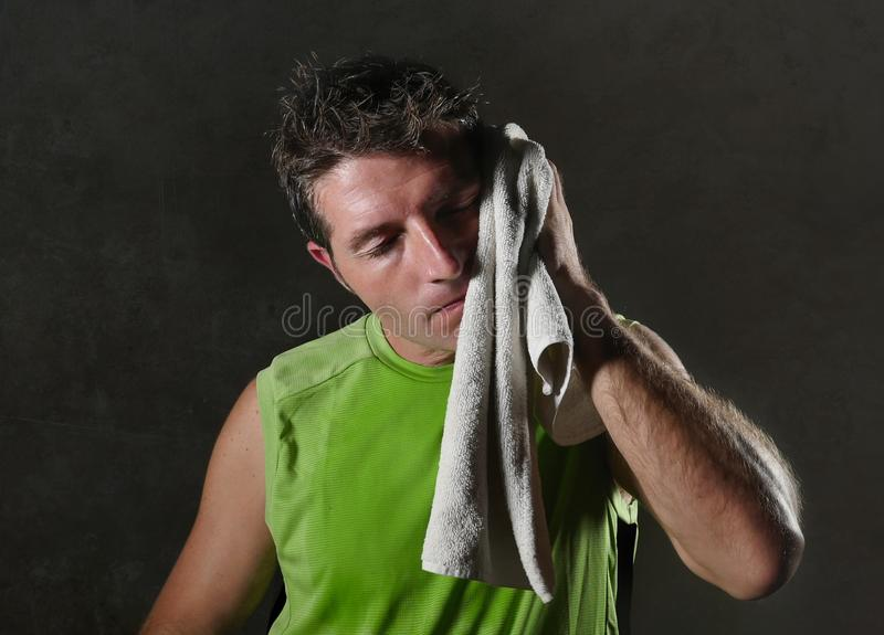 Young tired and exhausted sport man drying sweat with towel all sweaty and breathless after hard workout and fitness training royalty free stock image