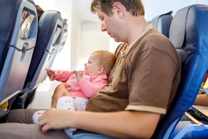 Young tired father and his crying baby daughter during flight on airplane going on vacations. Young sad tired father and his crying baby daughter during flight stock images