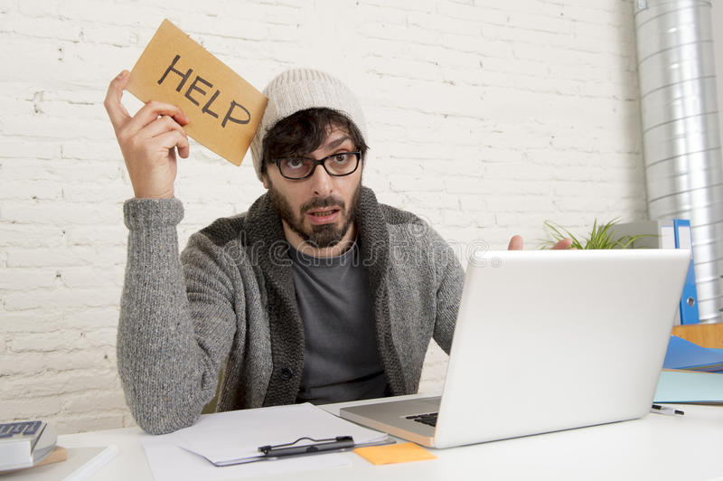 Young tired hispanic hipster businessman busy asking for help suffering stress. Busy hispanic hipster 30s businessman working tired at home office with computer stock image