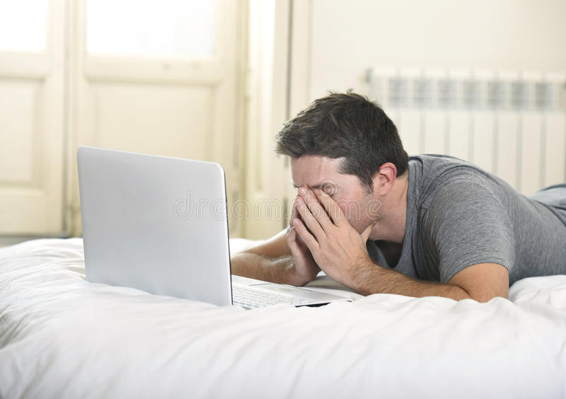 Young tired man lying on bed or couch working on computer laptop at home wireless connected to internet in technology concept stock photos