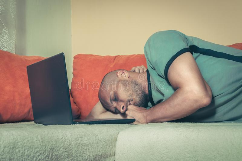 Young tired man taking a break and fell asleep on the bed with his lap top computer after hard and long online work, dark image stock photography