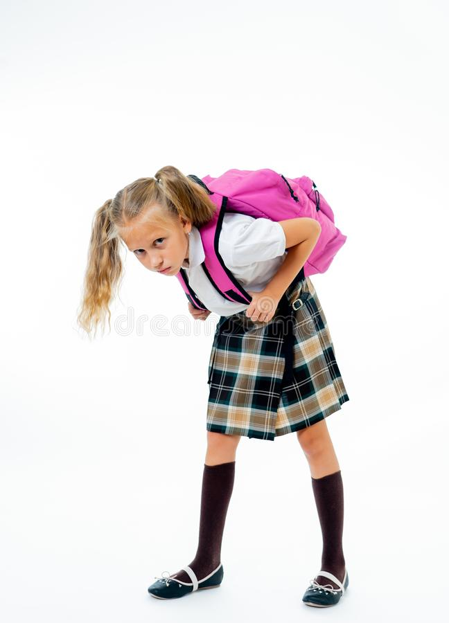 Young tired and sad cute school girl standing with a big heavy school bag on her back on a isolate white background for a back. Pain stress homework and back to stock photo