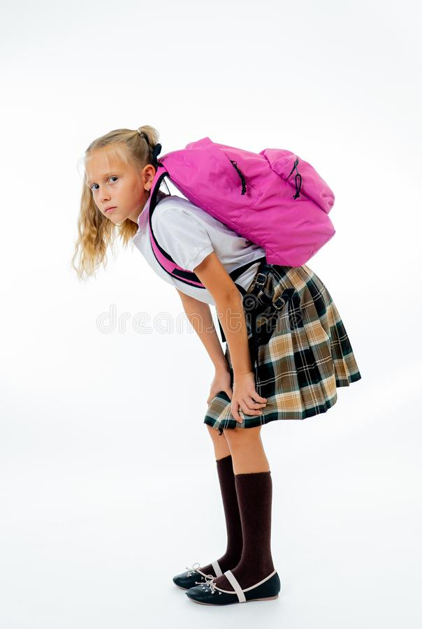 Young tired and sad cute school girl standing with a big heavy school bag on her back on a isolate white background for a back royalty free stock photos