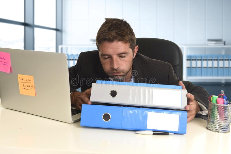 Businessman working in stress at office laptop computer looking exhausted and overwhelmed. Young tired and wasted businessman working in stress at office laptop stock image