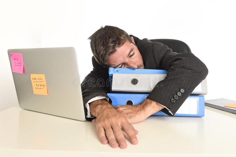 Young tired and wasted businessman working in stress at office laptop computer sleeping exhausted. Young tired and wasted businessman working in stress at office royalty free stock photography