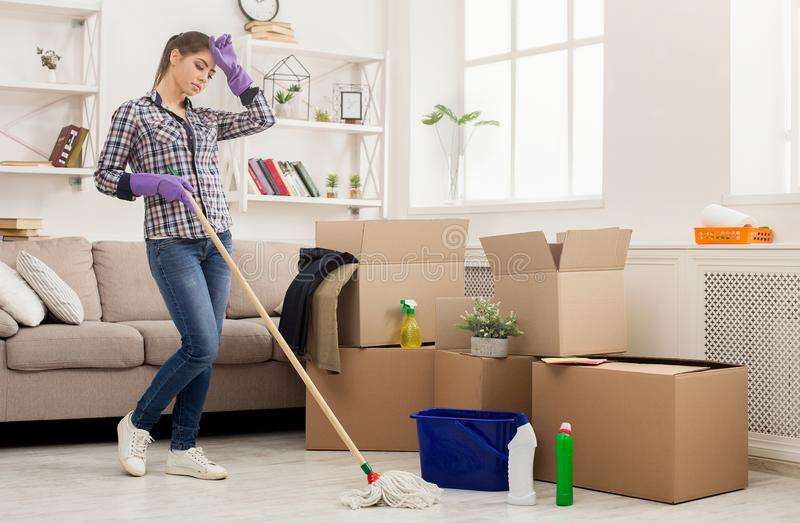 Young tired woman cleaning new home with mop stock photo