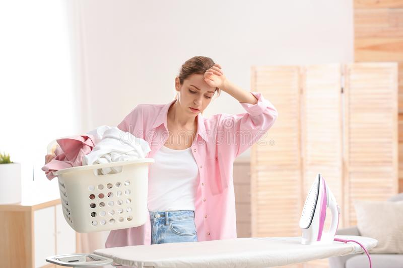 Young tired woman holding basket of clean laundry at ironing board stock image