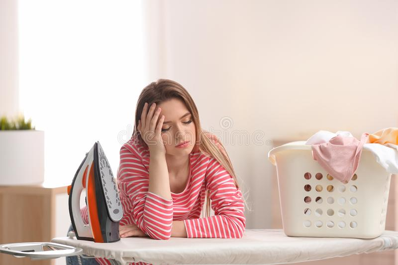 Young tired woman with iron and basket of clean laundry at board stock images