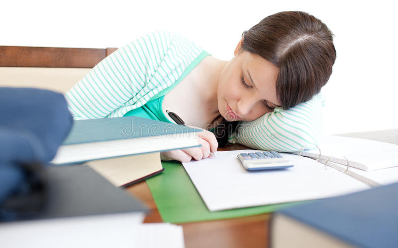 Young tired woman studying on a table stock image