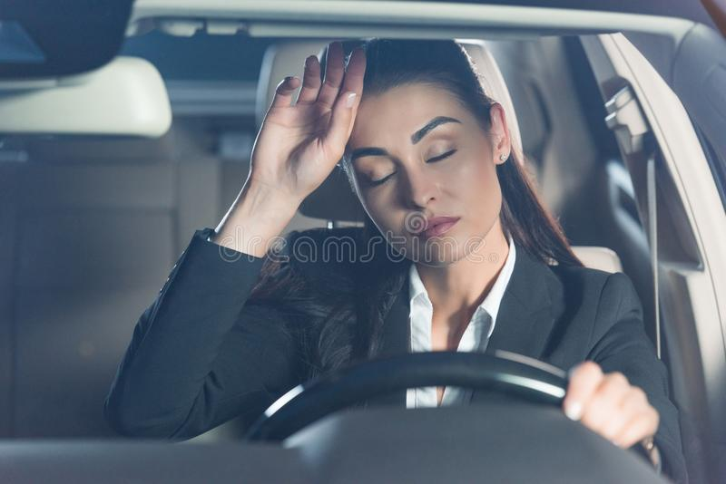 Young tired woman in suit sitting in driver seat and touching stock images