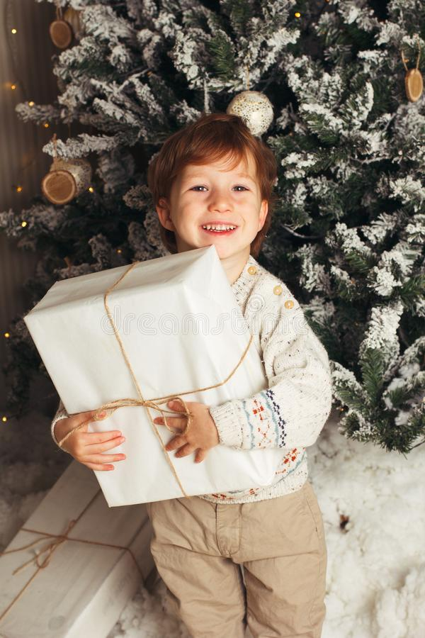 Young toddler Caucasian Boy Holding Christmas Present In Front Of Christmas Tree. Cute happy smiling boy. Vertical photo royalty free stock photography