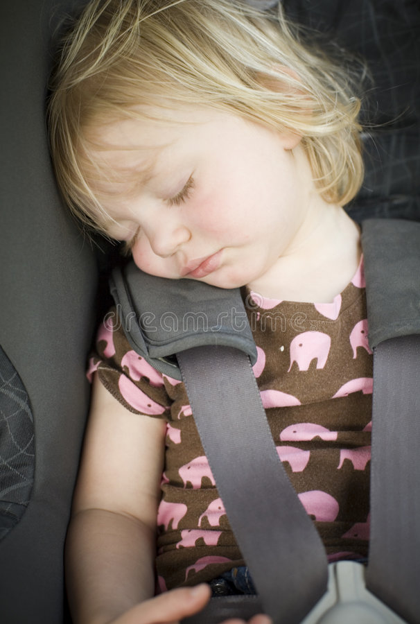 Young toddler girl in car seat stock image