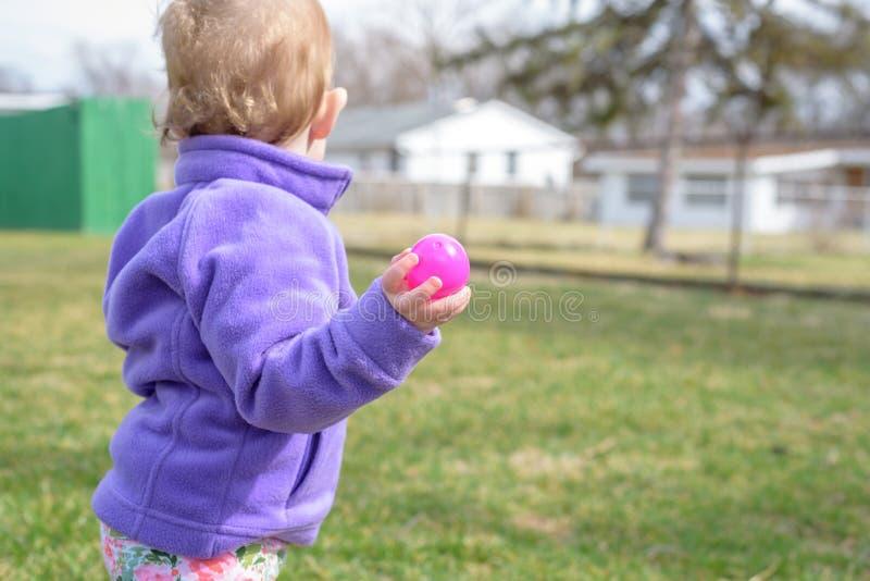 Young toddler girl holding Easter egg stock photos