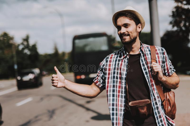 Young Tourist with Backpack Hitchhiking on Road stock image