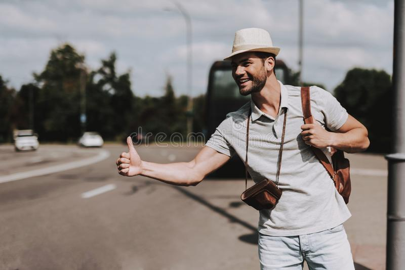 Young Tourist with Backpack Hitchhiking on Road. Casually dressed Handsome Man with Camera on Neck trying to Catch Car on Highway. Tourism and People Concept stock photos