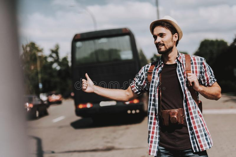 Young Tourist with Backpack Hitchhiking on Road. Casually dressed Handsome Man with Camera on Neck trying to Catch Car on Highway. Tourism and People Concept royalty free stock images