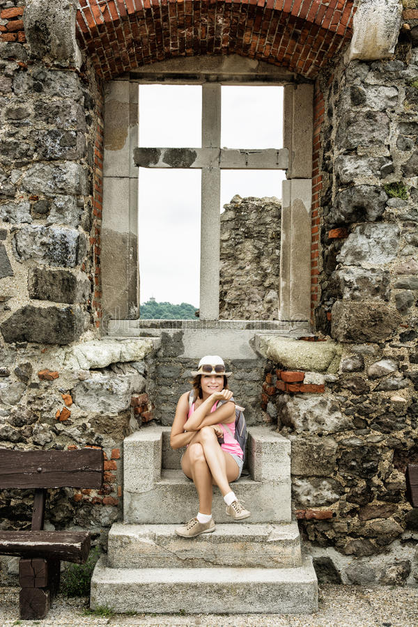 Young tourist caucasian woman posing with ancient window, Visegrad, Hungary. Young tourist caucasian woman posing with ancient window in ruin castle of Visegrad stock image