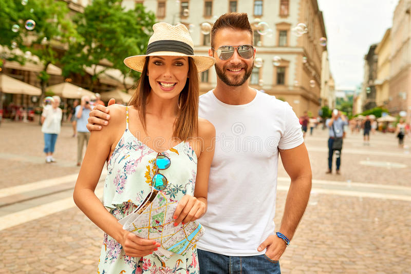 Young tourist couple. A beautiful young couple are standing with soap bubbles behind them at the St. Stephens Square in Budapest, Hungary royalty free stock photo
