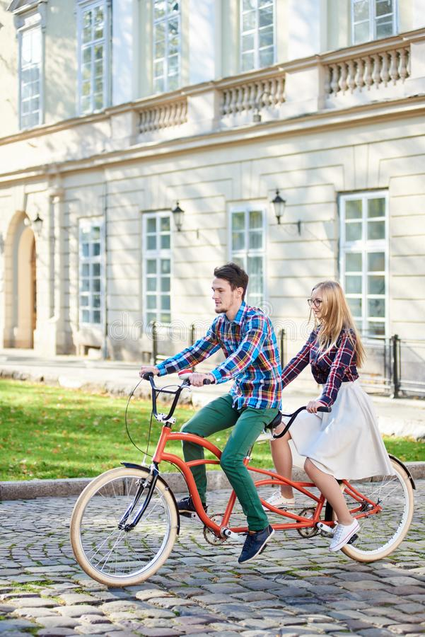 Young tourist couple, handsome man and pretty blond woman riding tandem bicycle along city street. royalty free stock photo