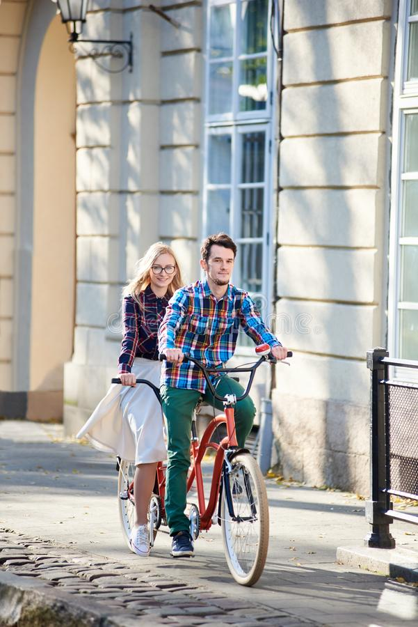 Young tourist couple, handsome man and pretty blond woman riding tandem bicycle along city street. stock images