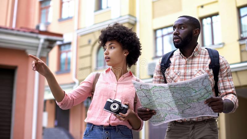 Young tourist couple with map and photo camera, choosing direction, travel royalty free stock photos