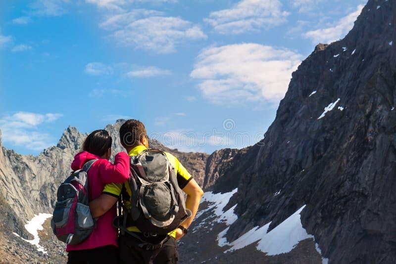 Young tourist couple standing on stone near mountain lake royalty free stock photo