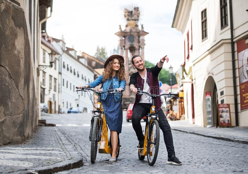 Young tourist couple travellers with electric scooters in small town. royalty free stock photography