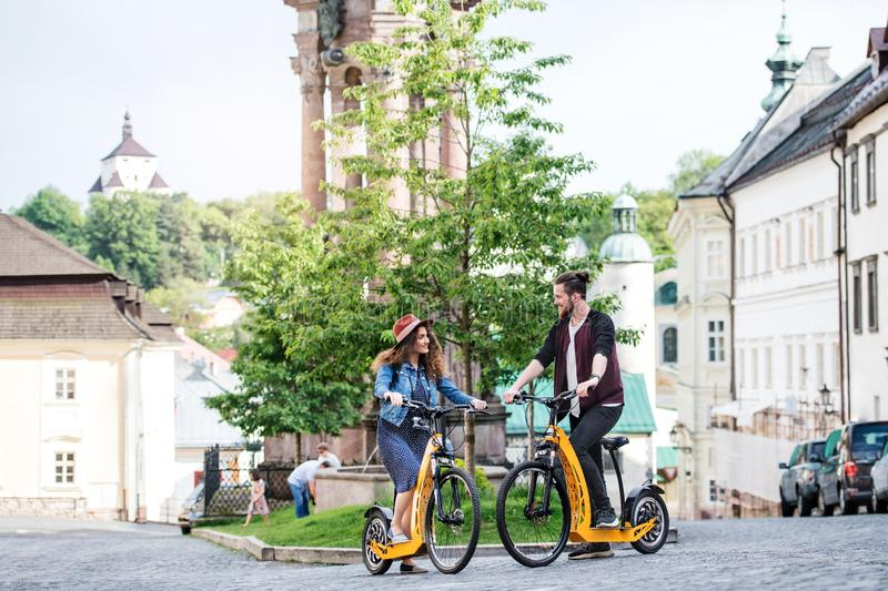 Young tourist couple travellers with electric scooters in small town, talking. royalty free stock photography