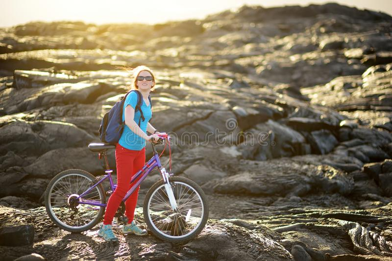 Young tourist cycling on lava field on Hawaii. Female hiker heading to lava viewing area at Kalapana on her bike. Tourist on hike. Young tourist cycling on lava royalty free stock photos