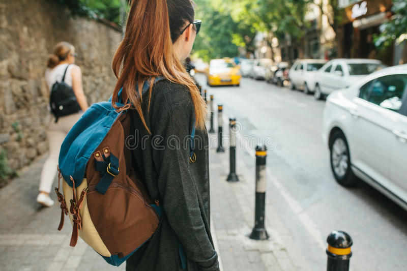 A young tourist girl with a backpack in the big city is waiting for a taxi. Journey. Sightseeing. Travel. royalty free stock photography