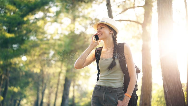 Young tourist girl backpacker in hat chatting with smartphone during walking in summer forest royalty free stock images