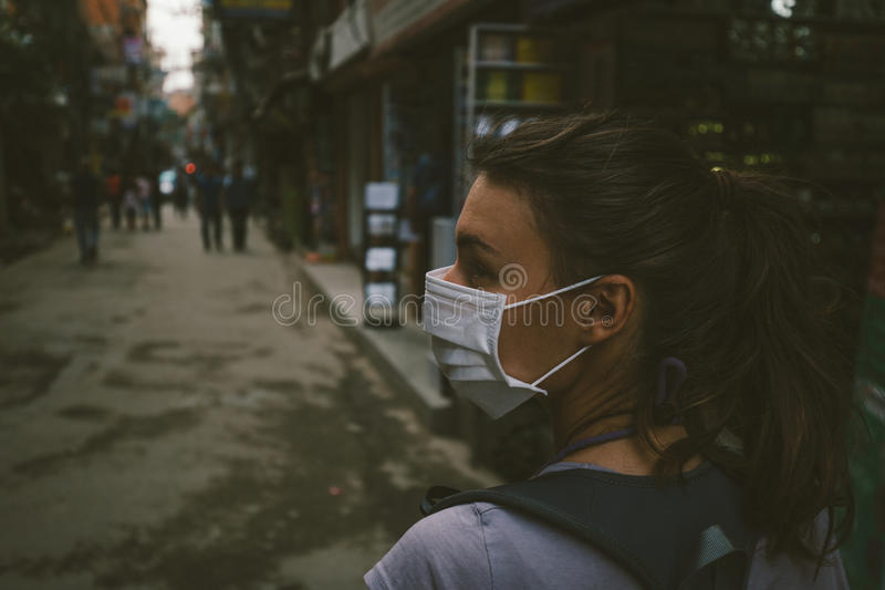 Young tourist girl with face mask. Young woman with face mask in the streets of Kathmandu royalty free stock photos