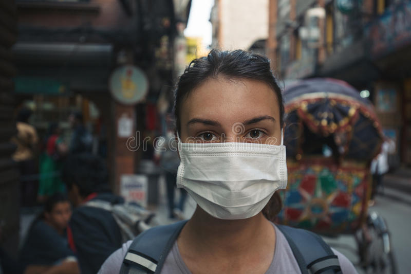 Young tourist girl with face mask. Young woman with face mask in the streets of Kathmandu royalty free stock image
