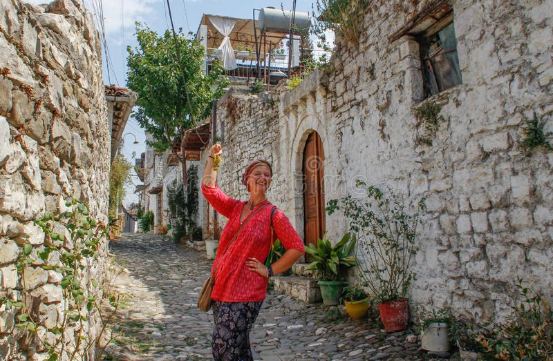 A young tourist girl in a pink blouse is standing on a cobbled road in the ancient Albanian town of Berat, overlooking the medieva stock images