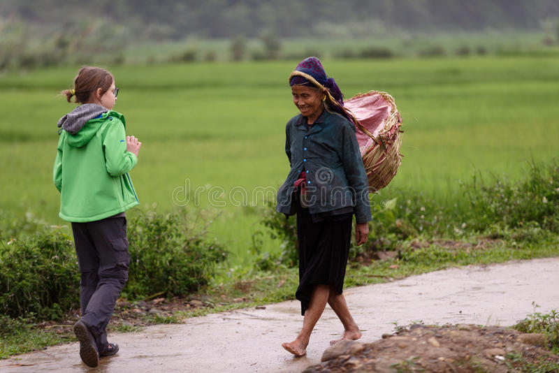 Young tourist greeting old Vietnamese woman on road. A young tourist greets an old Vietnamese woman from Thai tribe on a road passing through rice fields in Sa royalty free stock photography